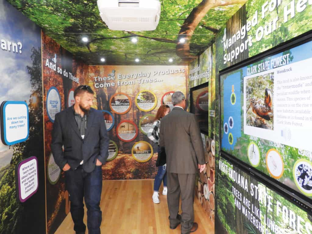 Members of IHLA tour the inside of the Woods on Wheels exhibit.