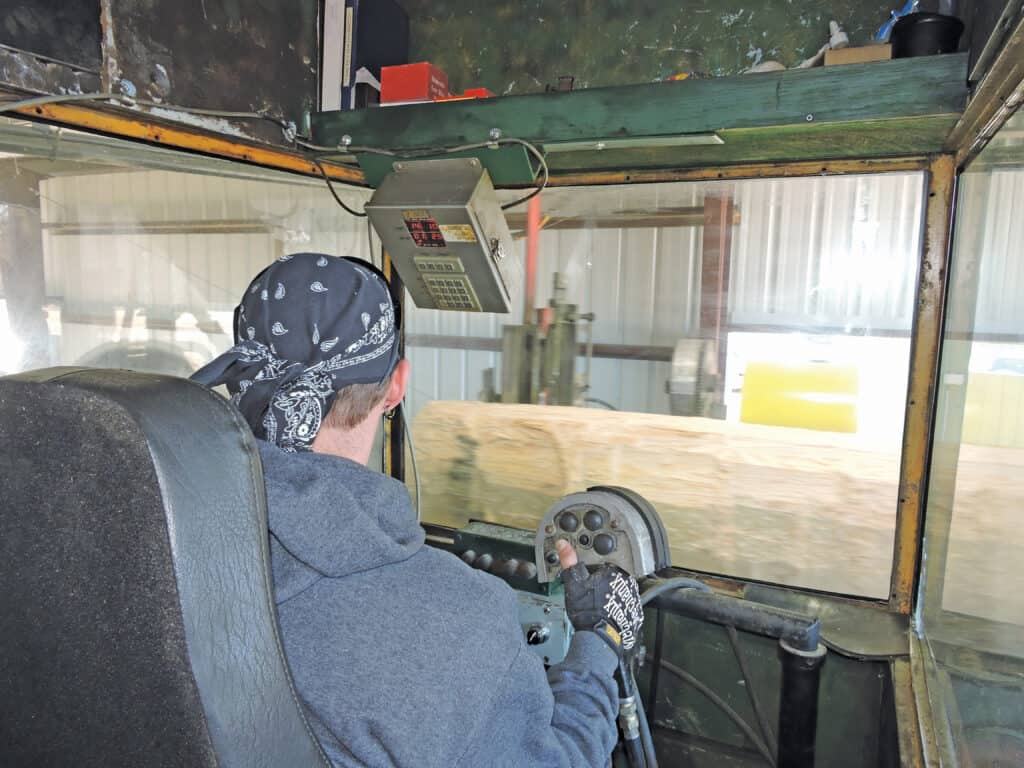 Cody Gray works in the cab at Prime Lumber Sawmill to control the precision-sawing of lumber.