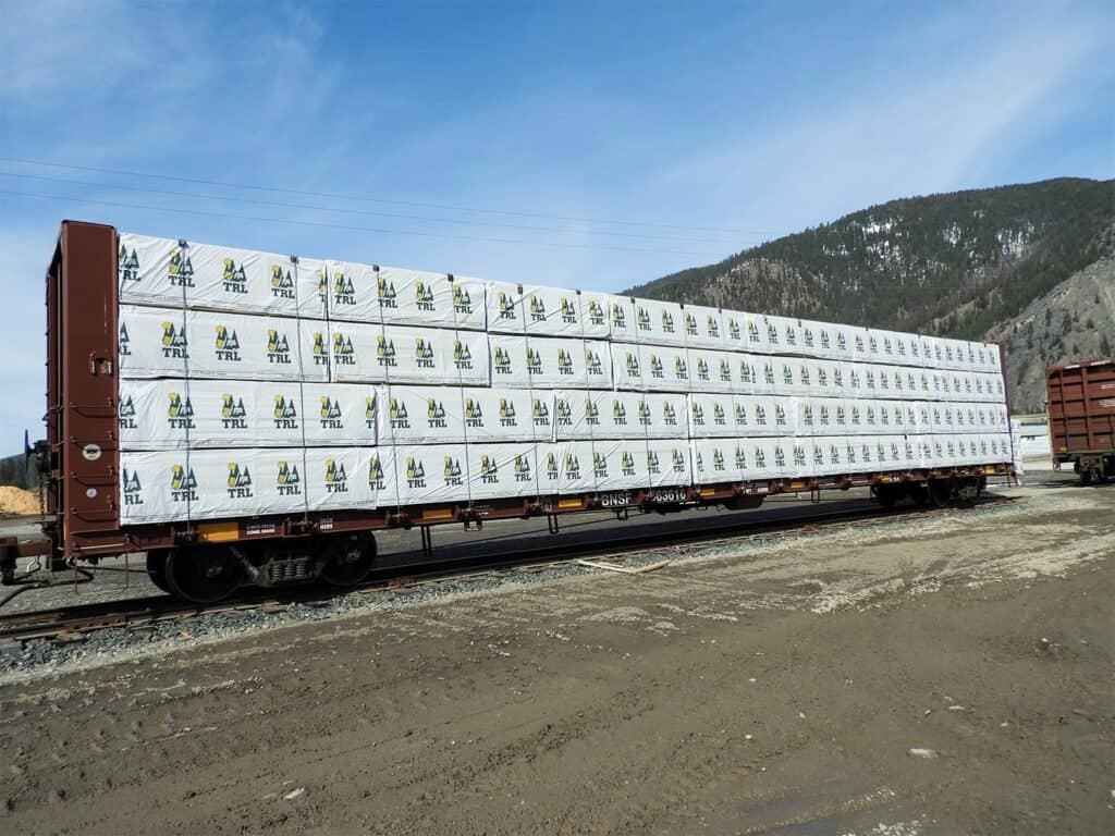 A rail car is loaded to the max with high-quality lumber, carrying the Thompson River Lumber logo.