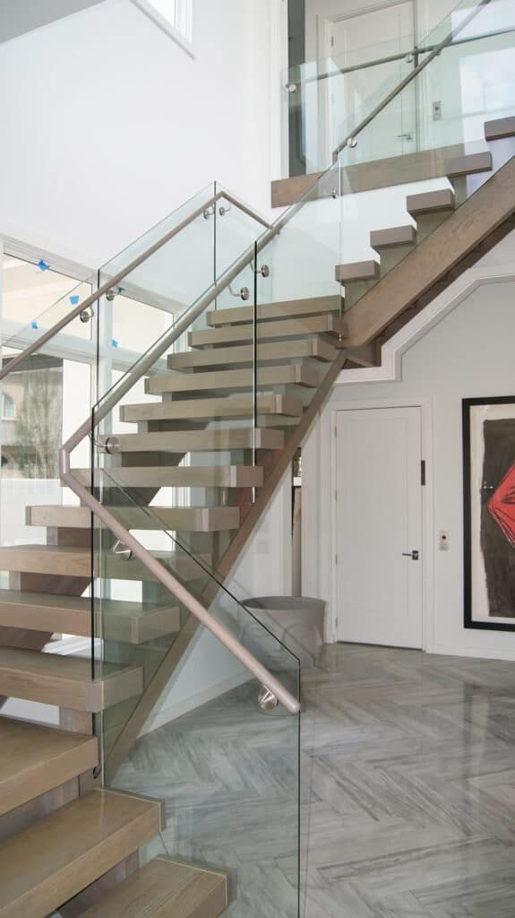 This freestanding curve stair with Red Oak treads, Poplar closed stringers with custom wrought iron rails was crafted by Vision Stairways and Millwork.